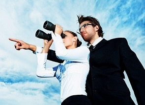 woman with binoculars and man behind her